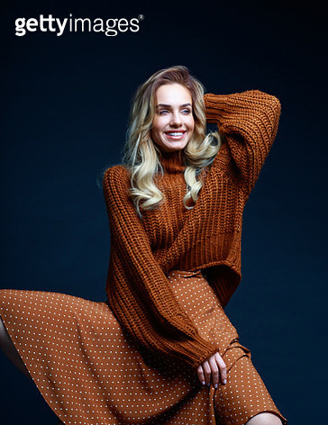 Fashion portrait of long hair blond young woman wearing brown sweater and skirt, laughing with raised hand. Studio shot against black background. - gettyimageskorea