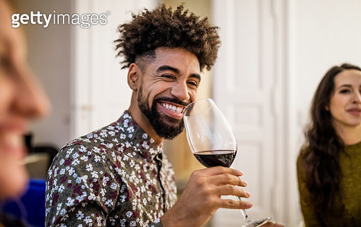Smiling young man drinking red wine during dinner party at home - gettyimageskorea