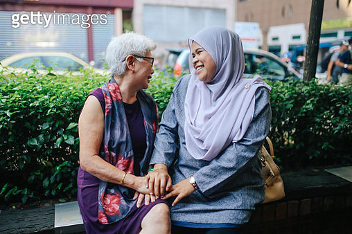 Vintage toned image of two Malaysian women, talking and enjoying the beautiful day in Kuala Lumpur. They're old friends or just neighbors stopped for a chat. - gettyimageskorea