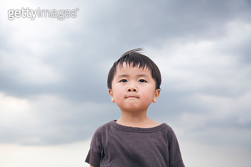 Boy standing under a cloudy sky - gettyimageskorea