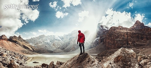 Rear View Of Man Looking At Mountains While Standing On Rock Against Sky - gettyimageskorea