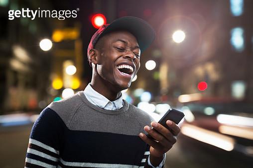 Man laughing at phone in urban street at night. - gettyimageskorea