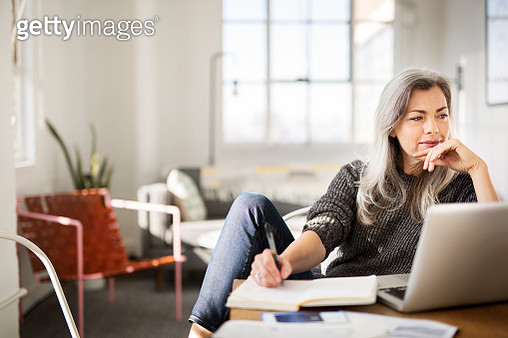 Mature woman writing in diary while working at home - gettyimageskorea