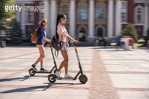 Girlfriends riding e-scooters in the city - gettyimageskorea