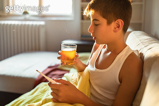 Sick child boy sitting in bed with a fever - gettyimageskorea