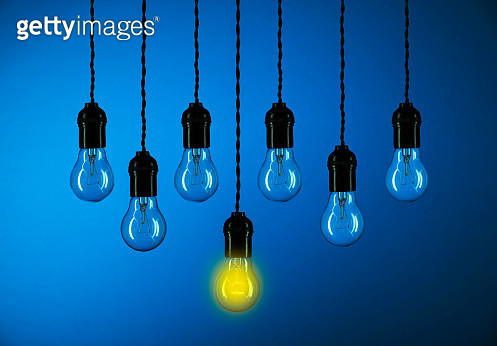 Close-Up Of Light Bulb Hanging Against Blue Background - gettyimageskorea