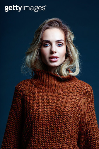 Fashion portrait of long hair blond young woman wearing brown sweater, looking at camera. Studio shot against black background. - gettyimageskorea