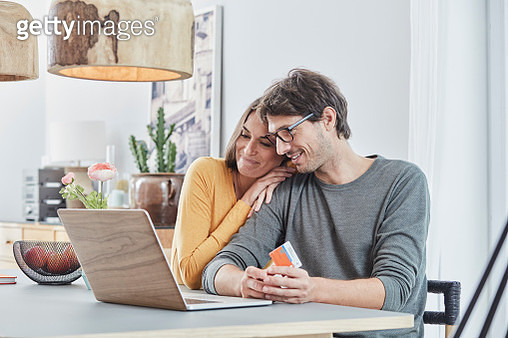 Smiling couple with a card using laptop on table at home - gettyimageskorea
