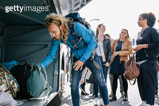 A Group Of Young Travellers Loading A Coach With Their Bags - gettyimageskorea