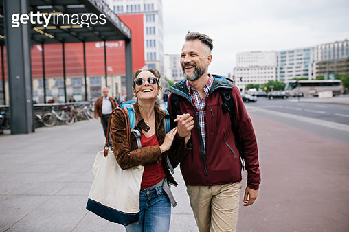 A mature couple are holding hands and smiling as they walk through Berlin together on a day trip. - gettyimageskorea