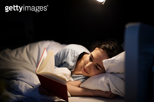 Woman reading book in bed - gettyimageskorea
