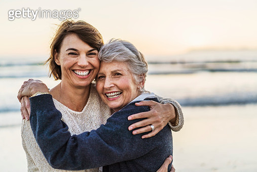 A photo of happy mother embracing female. Portrait of daughter with senior woman. They are at beach. - gettyimageskorea