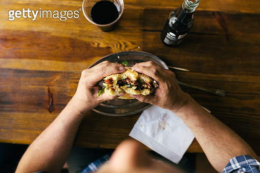 An aerial view of a man eating a burger and drinking cola in a restaurant. - gettyimageskorea
