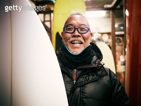 There is a man with a smile next to the surfboard in the surf shop - gettyimageskorea
