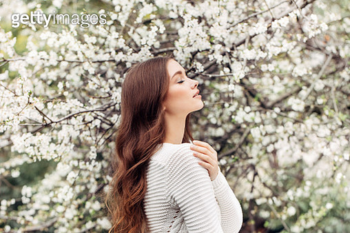 Beautiful girl on the background of spring bush - gettyimageskorea
