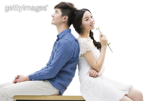 Happy young couple back to back - gettyimageskorea
