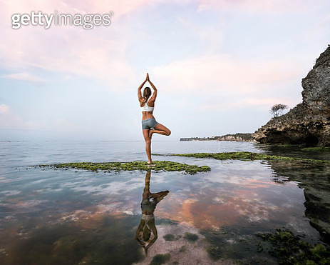 Asia, Indonesia, Bali, Uluwatu, young woman practicing yoga in front of rockpool at seashore, showing reflection in water - gettyimageskorea