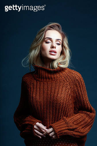 Fashion portrait of long hair blond young woman wearing brown sweater, looking away. Studio shot against black background. - gettyimageskorea
