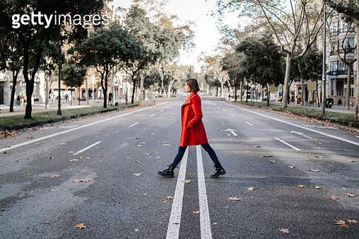 Fashionable woman wearing winter jacket walking on road - gettyimageskorea