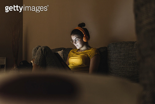 Woman with headphones listening to music on couch at home - gettyimageskorea