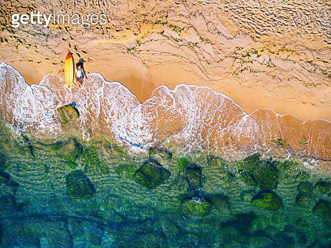 Aerial view of a surfer girl resting on a beach - gettyimageskorea