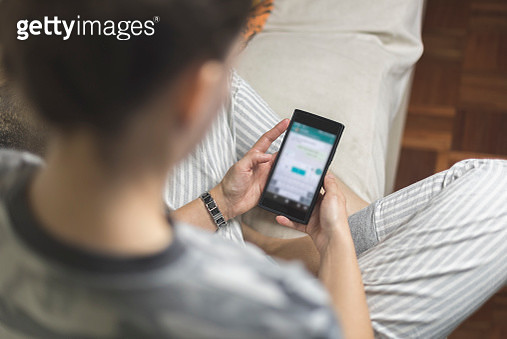 Young woman using her smart phone sitting on the couch at home - gettyimageskorea