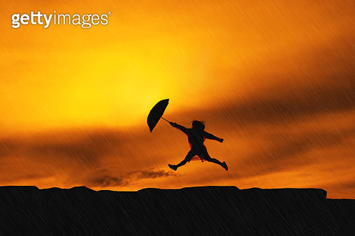 Silhouette Woman Holding Umbrella Jumping Against Sky During Sunset - gettyimageskorea