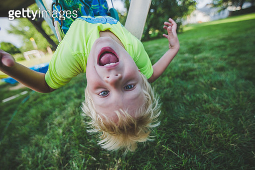 Little boy hangs upside down from a swing set swing smiling with his mouth wide open and his hair sticking up. - gettyimageskorea