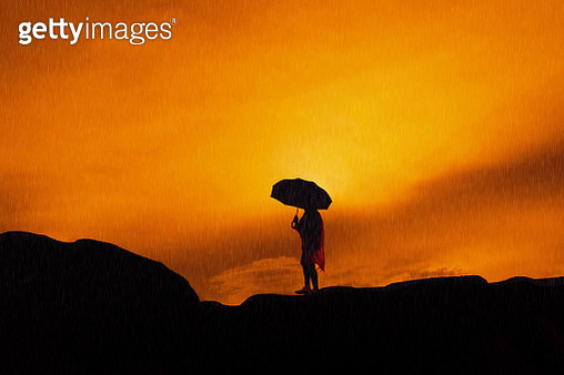 Silhouette Woman Holding Umbrella Against Sky During Sunset - gettyimageskorea