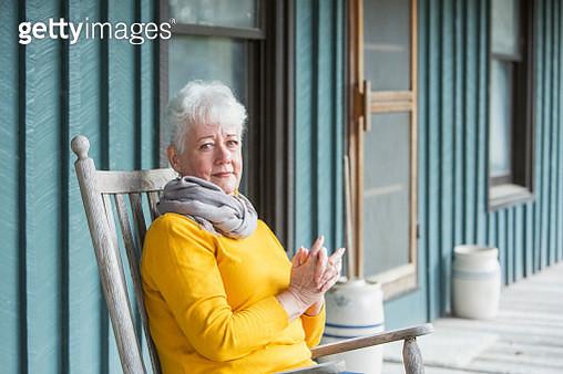 Serious senior woman sitting in rocking chair - gettyimageskorea