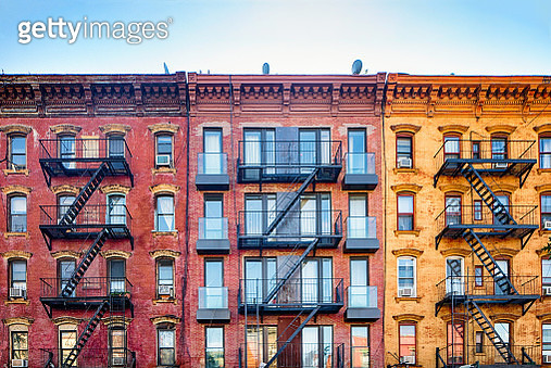 Top stories of colorful Williamsburg apartment buildings with steel fire escape stairways - gettyimageskorea