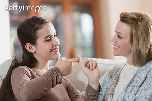 Teenage girl with mother, using sign language - gettyimageskorea