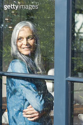 Senior woman looking out of window, smiling - gettyimageskorea