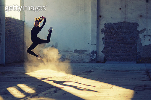 Silhouette of ballerina dancing in an abandoned building on a sunny day. - gettyimageskorea