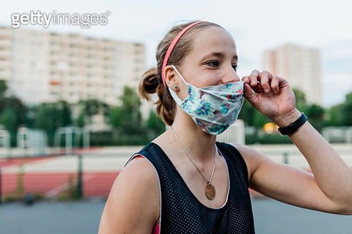 Woman putting on colorful facemask - gettyimageskorea