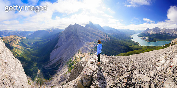 A woman stands on top of a natural feature known as the Rimwall. To the far left is the Bow Valley, followed by the Wind Valley. Mount Lougheed is seen in the center. The Spray Lakes valley is seen on the right. - gettyimageskorea