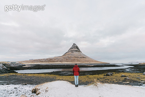 Woman near  Kirkjufell mountain in Iceland in winter - gettyimageskorea