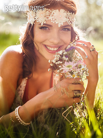 Smiling hippie girl in a park holding wild flowers - gettyimageskorea