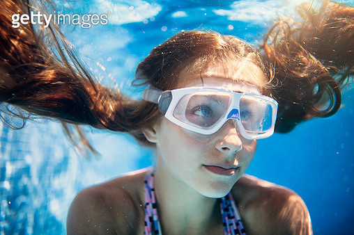 Close-up of a cute teenage girl swimming underwater. Shot with Nikon D850 - gettyimageskorea