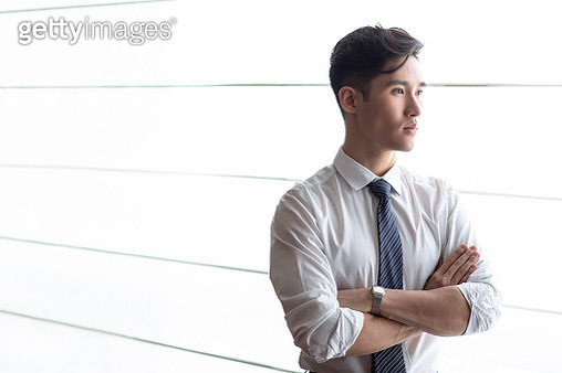 Young businessman thinking in front of hotel window - gettyimageskorea