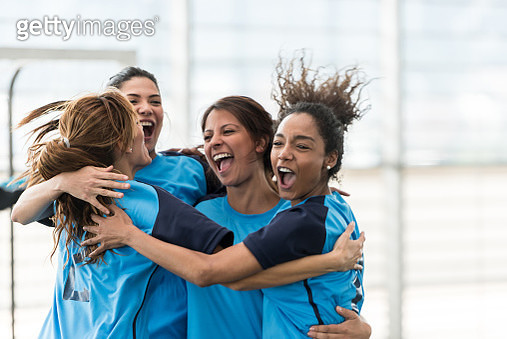 Excited female soccer players hugging after scoring a goal - gettyimageskorea