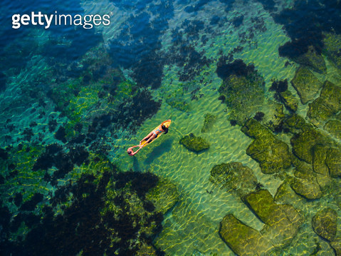 Aerial view of a couple having fun on a sea water with surf - gettyimageskorea