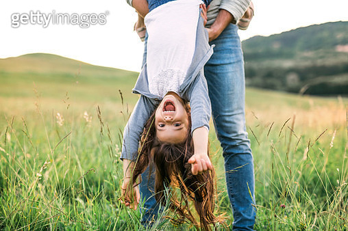 A father holding a happy small girl upside down outside in spring nature. - gettyimageskorea