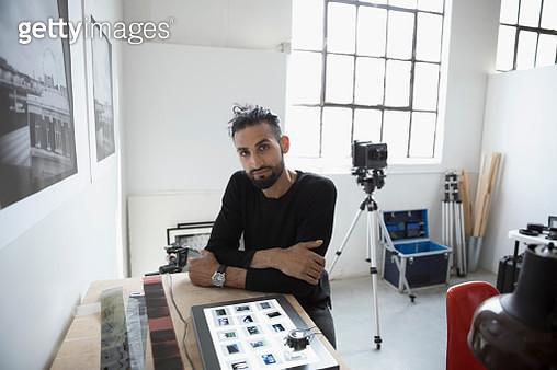 Portrait confident male photographer reviewing photographic slides in art studio - gettyimageskorea