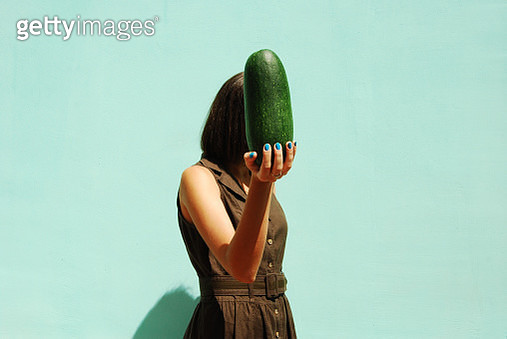 Woman Holding Large Cucumber Over Green Background - gettyimageskorea