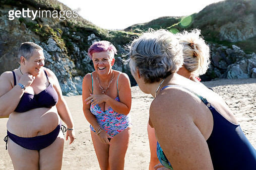 A group of women swimmers getting ready for a swim on an empty beach - it's a bright and sunny autumn day. - gettyimageskorea