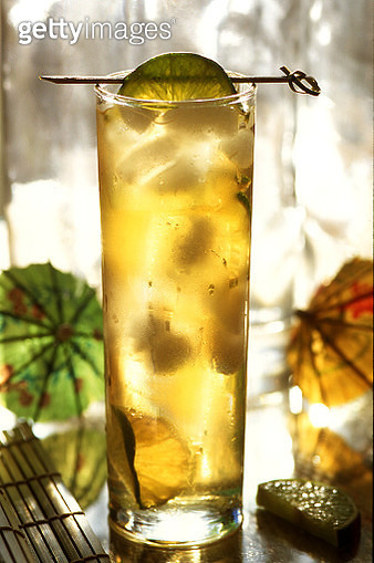 Infused iced tea or cocktail with a fruit garnish in a colorful, tropical setting with cocktail umbrellas and bamboo - gettyimageskorea