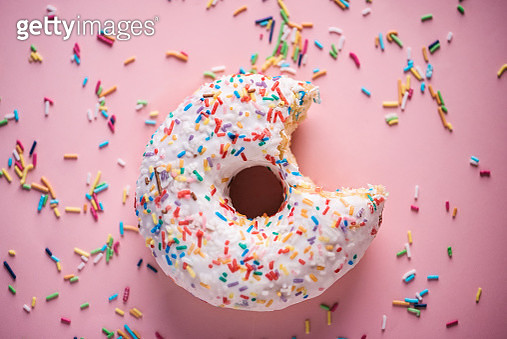 Close-up of white donuts with multi colored sparks on pink background - gettyimageskorea