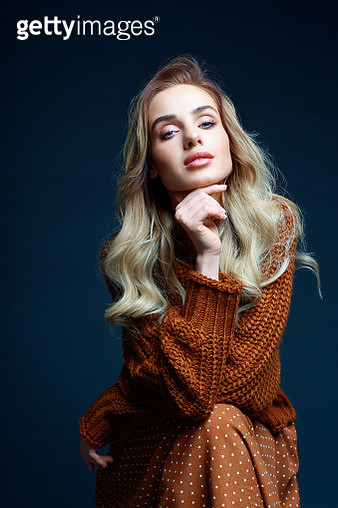 Fashion portrait of long hair blond young woman wearing brown sweater and skirt, smiling at camera. Studio shot against black background. - gettyimageskorea