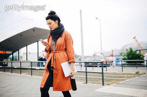 Young commuter woman, walking in Berlin, carrying her laptop, checking apps on the mobile phone. - gettyimageskorea